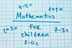 The word `mathematics for children` with tasks in a notebook for drawing. stock image