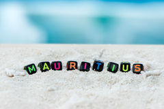 Word Mauritius wordt gemaakt van multicolored brieven op sneeuwwit zand tegen het blauwe overzees Royalty-vrije Stock Afbeeldingen