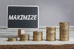 Word Maximize in white chalk. Type on black board, Euro money coin stacks of growth on wood table stock images