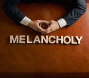 Word Melancholy and devastated man composition. Word Melancholy made of wooden block letters and devastated middle aged caucasian man in a black suit sitting at royalty free stock photography