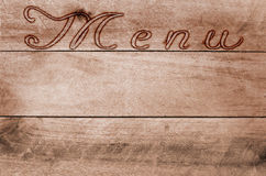 Word menu written, burned lettering on wooden brown background Stock Photography