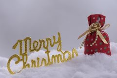 Word merry chrismas with bag in snow. Word merry chrismas with a bag in snow Royalty Free Stock Photography