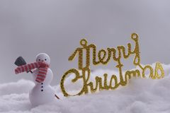 Merry chrismas with a snowman in snow. Word merry chrismas with a snowman in snow Stock Photos