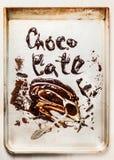 Word met vloeibare chocolade wordt gemaakt bakt dienblad dat stock afbeeldingen