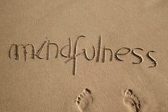 Word mindfulness in het zand stock fotografie