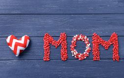 Word MOM composed of sprinkles on wooden background. Mother's Day stock photography