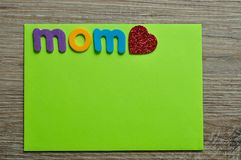 The word mom with a red heart on a green note. On a wooden background Stock Photo