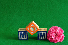 The word mom spelled with alphabet blocks. Against a green background with a pink flower stock photography