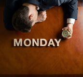 Word Monday and devastated man composition. Word Monday made of wooden block letters and devastated middle aged caucasian man in a black suit sitting at the stock photo