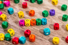 Word `money` of the colored wooden cubes on wooden desk.  Stock Photography