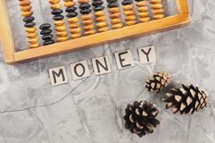 Word MONEY laid out of handwritten letters on cardboard squares near old wooden abacus and three cones. On gray cracked concrete royalty free stock image