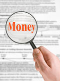 Word Money, magnifying glass in hand Royalty Free Stock Photo