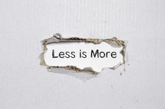 The word less is more appearing behind torn paper. Stock Photography