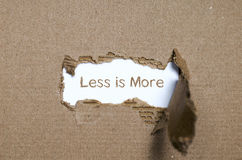 The word less is more appearing behind torn paper. Stock Image