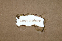 The word less is more appearing behind torn paper. Stock Images