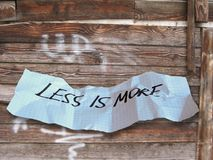 Word less is more on torned paper. On wood background Stock Photo