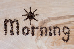 Word morning laid out from coffee grains on a wooden background. Word morning laid out from coffee grains on wooden background Stock Photo