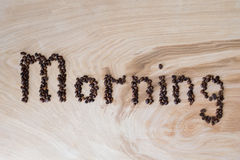 Word morning laid out from coffee grains on a wooden background. Word morning laid out from coffee grains on wooden background Royalty Free Stock Photography
