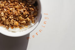 The word Morning stamped next to a bowl of muesli and yogurt wit. H hard shadow to convey outdoor dining Stock Photos