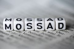 Word MOSSAD formed by wood alphabet blocks on newspaper. Closeup Royalty Free Stock Photo