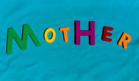 The word Mother composed from letters. The word Mother composed from colorful children toy big letters on the grass stock photography