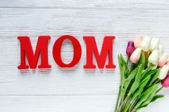 Word Mum from red letters and tender tulips on white wooden background. Mothers day decoration concept. Top view, flat lay stock images
