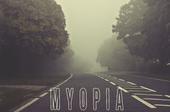 Word myopia written on foggy, blurred road, danger autumn road Stock Images