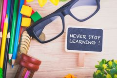 Word NEVER STOP LEARNING over scattered wooden workspace. Education concept,word NEVER STOP LEARNING over scattered wooden workspace royalty free stock photo