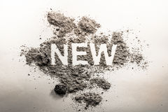 Word new written in ash, dust, dirt as a irony, oxymoron, parado Royalty Free Stock Photography