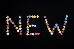 The word New is written in thick type of sugar pastry stars on a black background, for, advertising, commerce, sales stock photos
