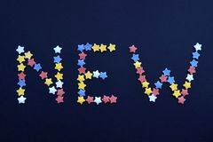 The word New is written in thin type of sugar pastry stars on a blue background, for, advertising, commerce, sales royalty free stock photos