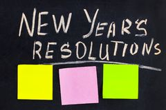 The word New Year`s resolution written on the blackboard with bl. Ank notes stock photo