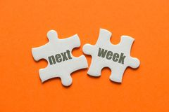 The word Next week on two matching puzzle on orange background.  royalty free stock photos