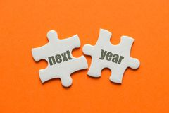 The word Next year on two matching puzzle on orange background.  royalty free stock image