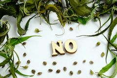 The word NO is laid out of wooden letters in the center of the frame from the dry leaves and the grains of the cannabis. stock images