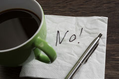 Word NO on napkin. No answer written on napkin and coffee cup on wooden table royalty free stock photo