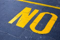 The word `no` painted in yellow. On gray asphalt Stock Photo