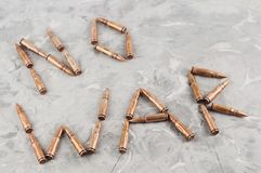 Word `NO WAR` laid out of bullets for assault rifle on old gray broken concrete. Word `NO WAR` laid out of metal bullets for assault rifle on old gray broken royalty free stock images