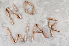 Word `NO WAR` laid out of metal bullets for assault rifle on gray broken concrete. Word `NO WAR` laid out of metal bullets for assault rifle on old gray broken stock image