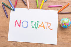 Word NO WAR in white paper with write from color crayon on bro. Top view word NO WAR in white paper with write from color crayon on brown wooden table royalty free stock photo