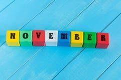 Word November op kleuren houten kubussen met licht Royalty-vrije Stock Foto's
