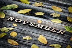 Word November, wooden letters. Frame of yellow leaves, wooden background Stock Photo