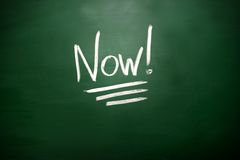 The word Now! on blackboard. A time management concept Royalty Free Stock Photography