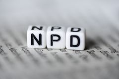 Word NPD formed by wood alphabet blocks on newspaper german party politics. Closeup Royalty Free Stock Images