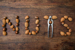 Word NUTS. Nutcracker with hazelnuts and almonds creating word NUTS on the wooden background Stock Photo