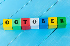 Word October on color wooden cubes with light blue Royalty Free Stock Photos