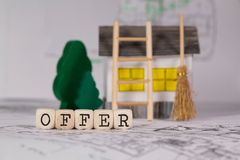 Word OFFER composed of wooden letter. Small paper house, wooden trees in the background. Closeup royalty free stock photography