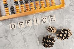 Word OFFICE laid out of handwritten letters on cardboard squares near old wooden abacus and three cones. On gray cracked concrete stock photography
