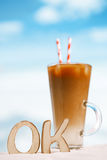 word OK with iced coffee latte on a beach ocean Royalty Free Stock Image
