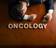 Word Oncology and devastated man composition. Word Oncology made of wooden block letters and devastated middle aged caucasian man in a black suit sitting at the stock photography
